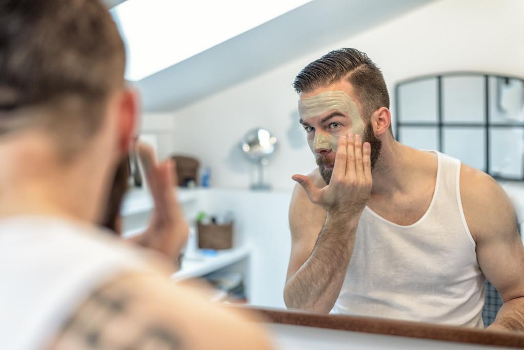 Mann mit Bart trgt eine Gesichtsmaske auf